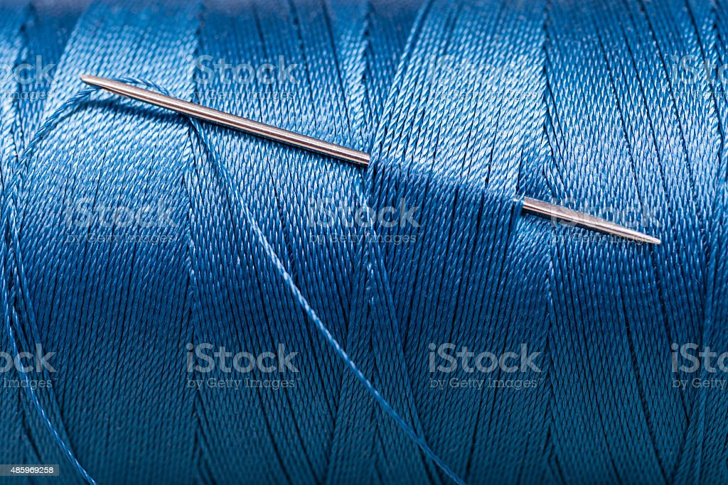 sewing needle in blue thread bobbin stock photo