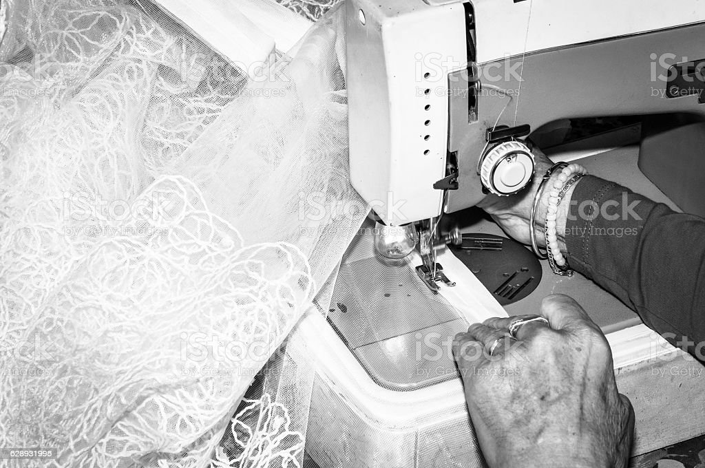 Sewing. Old woman sewing weeding dress stock photo