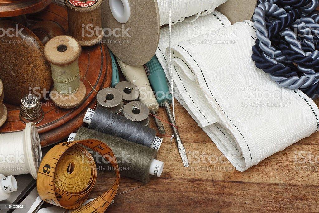 Sewing thread, fabric and tools on a wooden table royalty-free stock photo