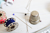 sewing tools and colored tape. Scissors, bobbins with thread and needles