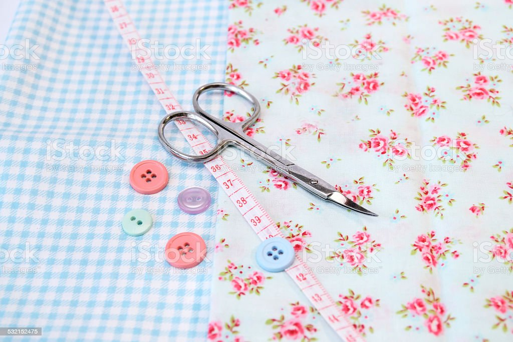 Sewing tools in vintage fabric background scissors and buttons stock photo