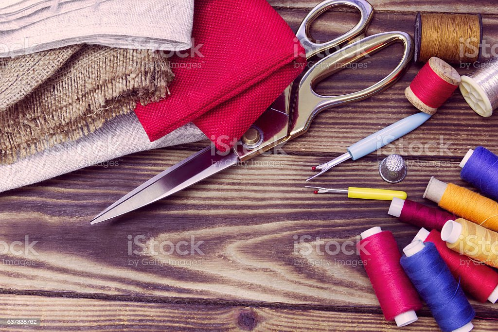 sewing tools, multi-coloured fabric and threads on a wooden back stock photo