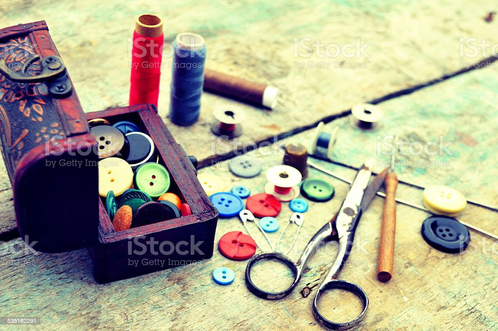 Sewing tools on a wooden background stock photo