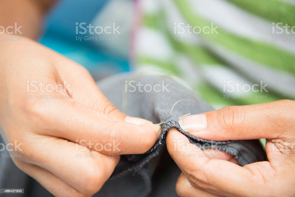 Sewing with needle and thread stock photo