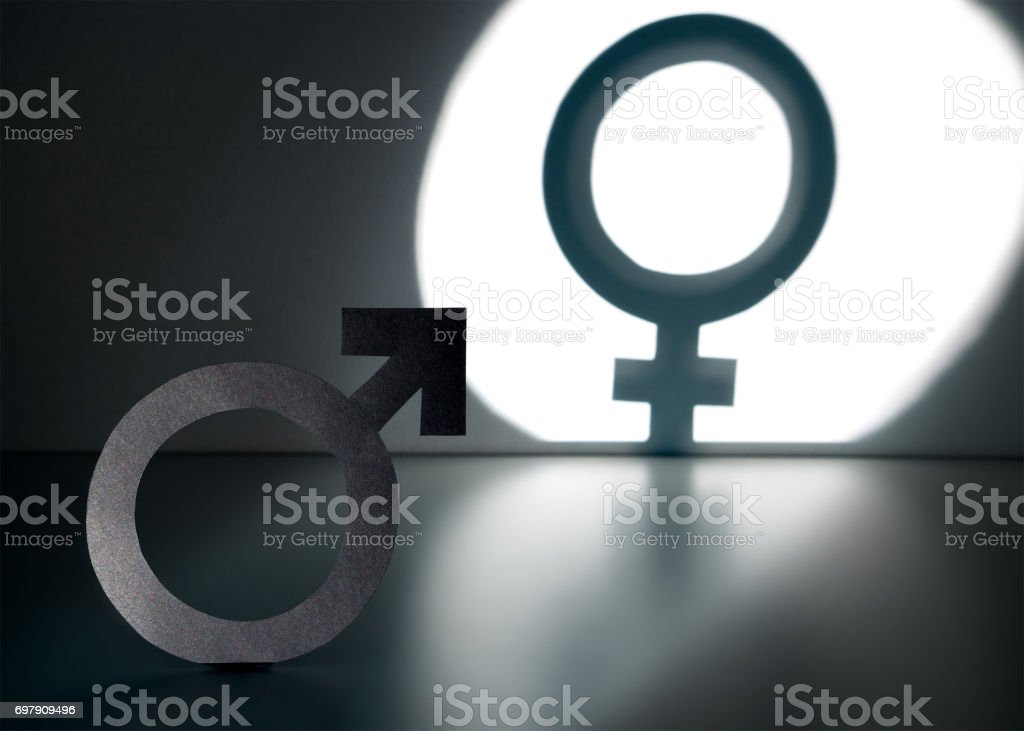 Sex change, gender reassignment, transgender and sexual identity concept. Male and man symbol in spotlight forming a female and woman sign in shadow on wall. stock photo