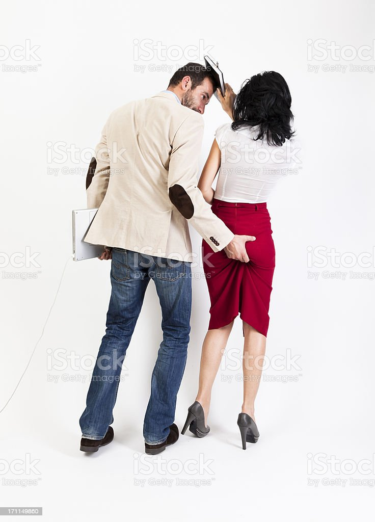 Sexual harassment. Woman hitting her colleague with the agenda stock photo