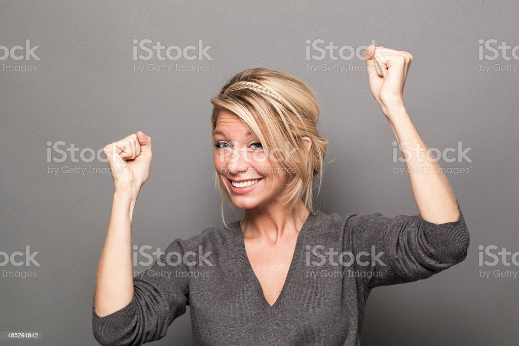 sexy 20s blonde woman dancing for success stock photo