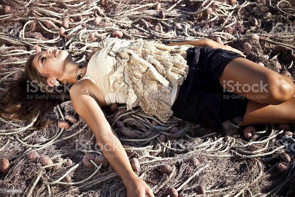 Sexy 20s Girl Lying Down On Fishing Net stock photo