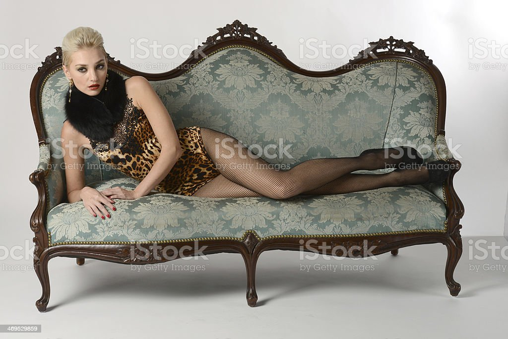 Sexy beautiful girl wearing lingerie sitting on a couch stock photo