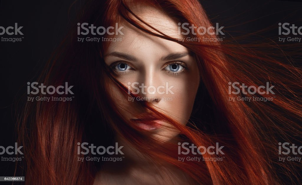 Sexy beautiful redhead girl with long hair. Perfect woman portrait on black background. Gorgeous hair and deep eyes. Natural beauty, clean skin, facial care and hair. Strong and thick hair. Flower stock photo