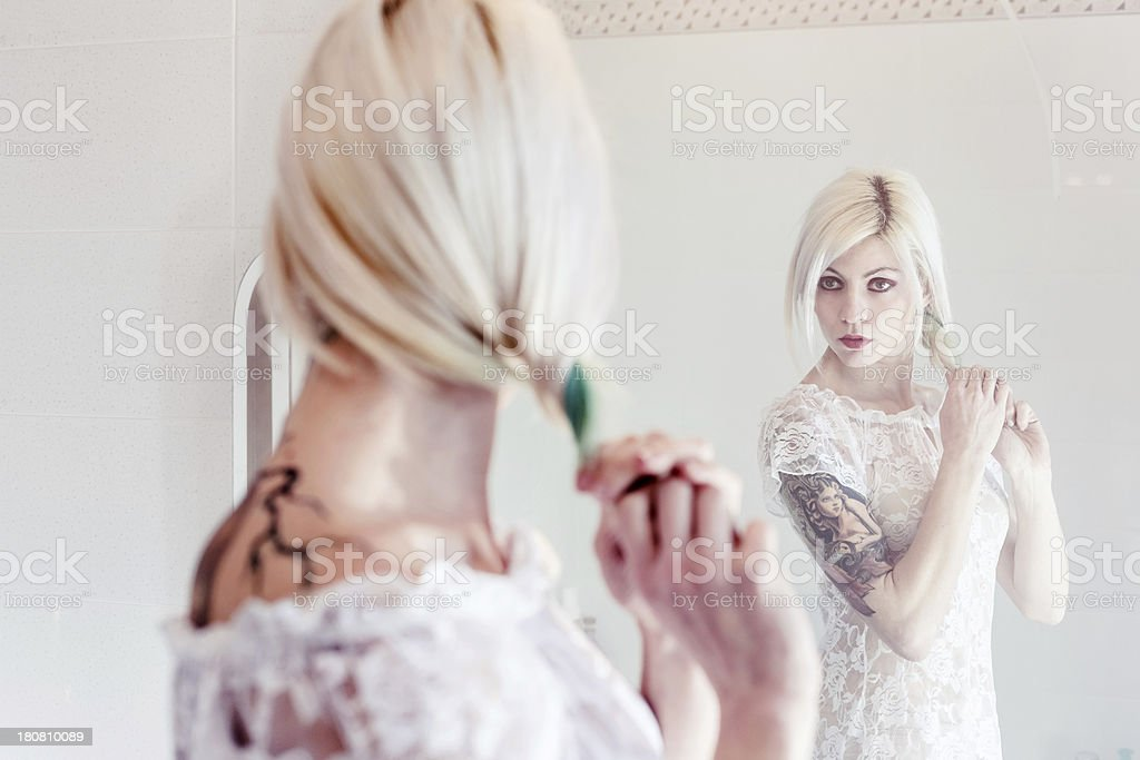 Sexy blond woman checking her hair royalty-free stock photo