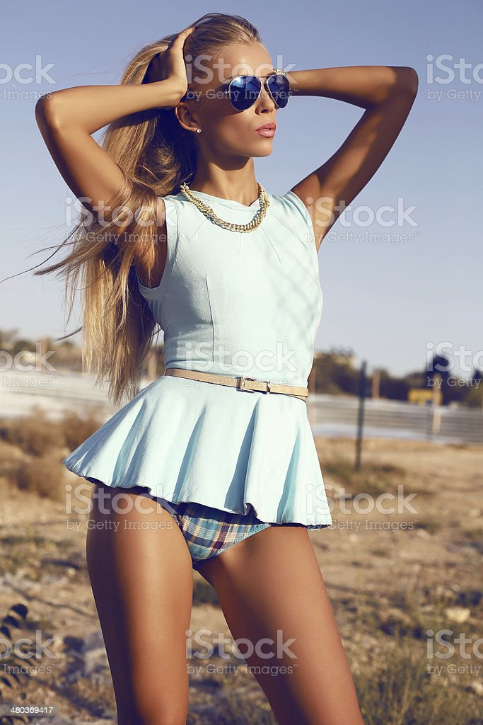 sexy blond woman in blue dress and aviator sunglasses stock photo