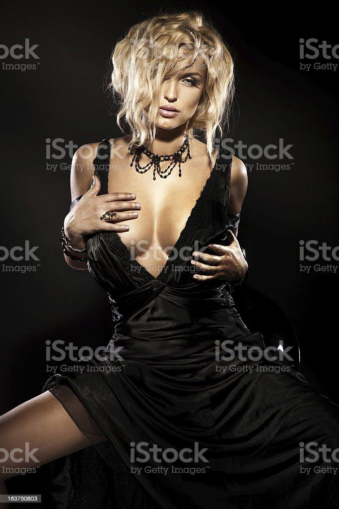 Sexy blonde beauty sitting in elegant black dress royalty-free stock photo