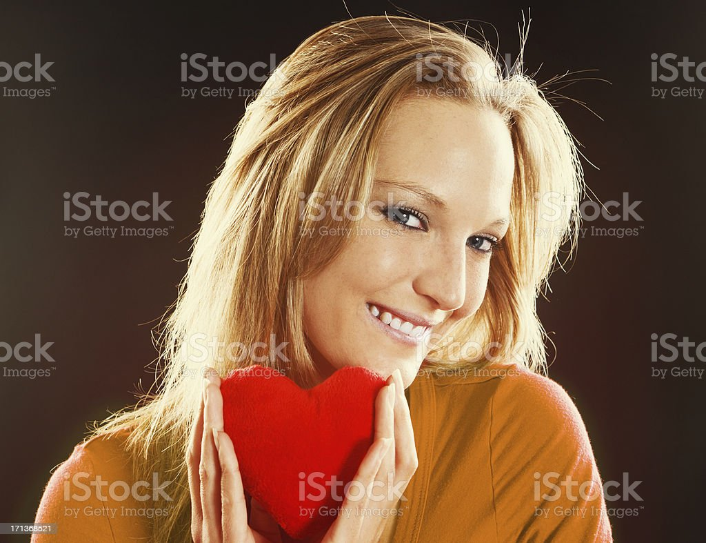 Sexy blonde with red Valentine heart smiles seductively stock photo