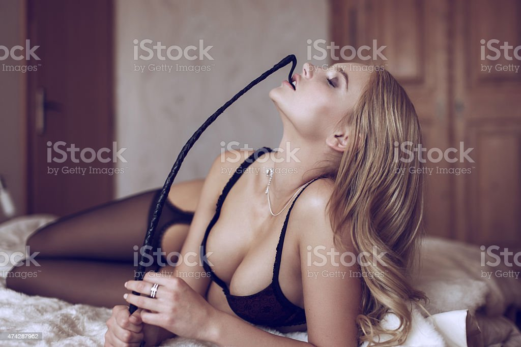 Sexy blonde woman in underwear bite whip stock photo
