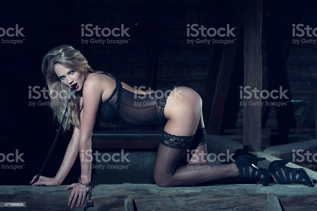 Sexy blonde woman kneeling with whip in barn stock photo
