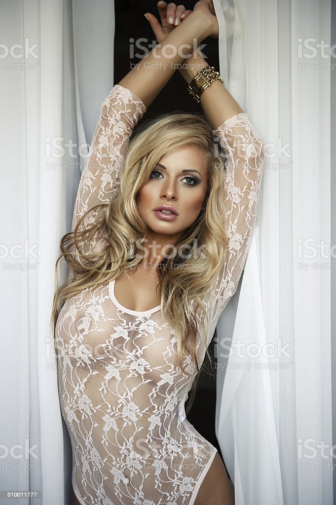 Sexy blonde woman with curtains stock photo