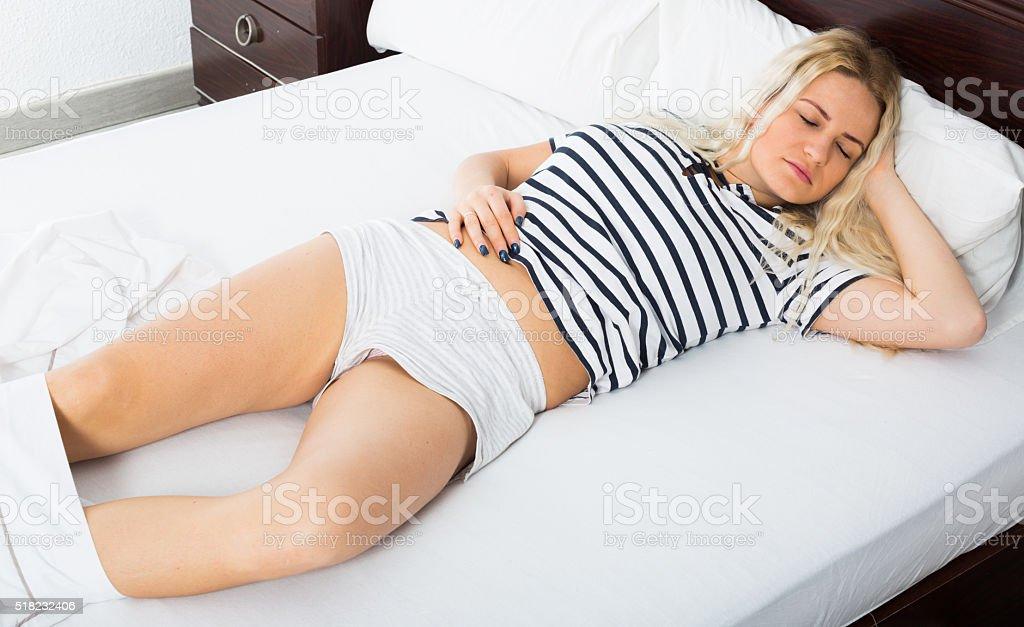 Sexy blondie sleeping in short pants stock photo