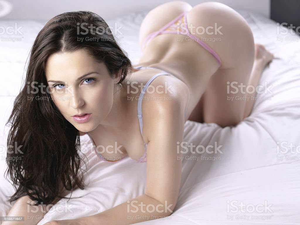 sexy blue eyed brunette posing on bed stock photo
