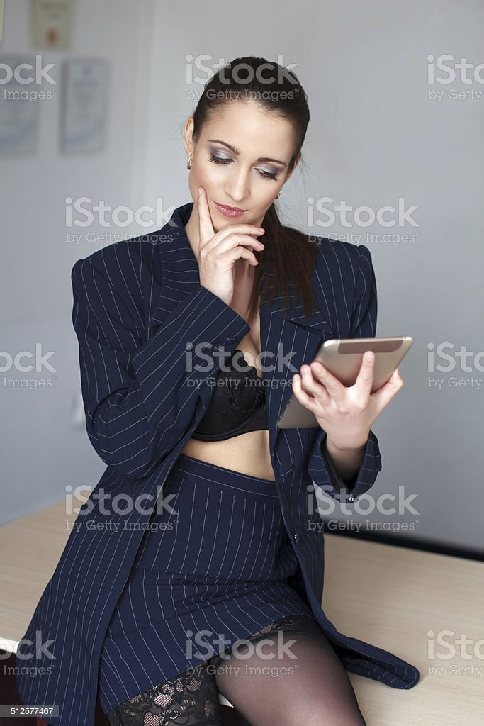 Sexy brunette CEO online flirt by tablet royalty-free stock photo