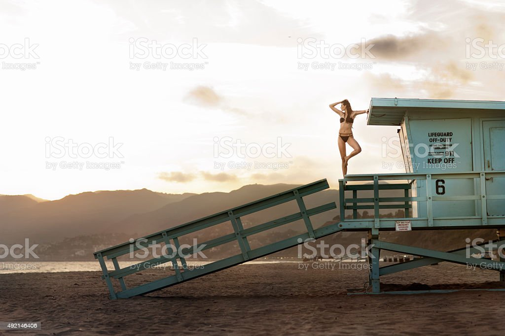 Sexy brunette in swimsuit on lifeguard stand stock photo