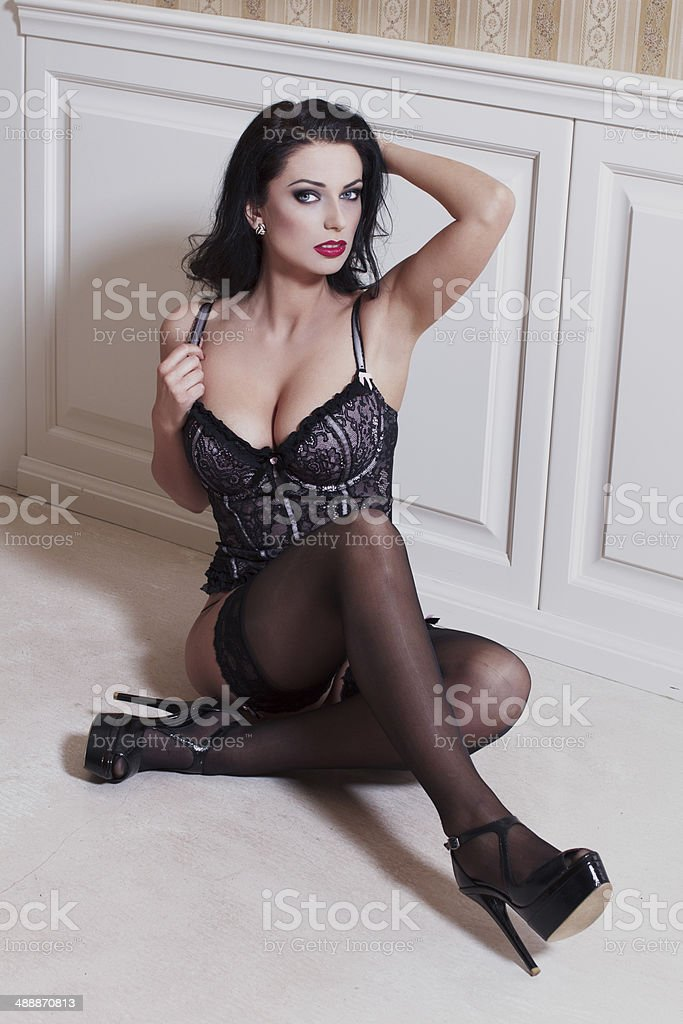 Sexy brunette model sitting on the floor at vintage wall royalty-free stock photo