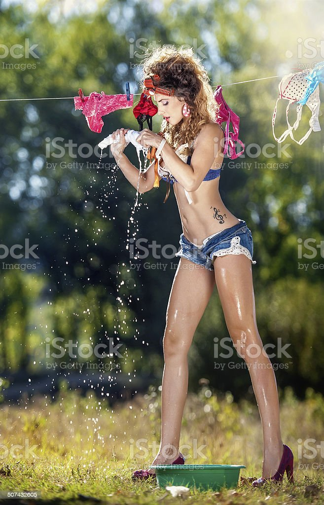 Sexy brunette putting wet clothes to dry in sun stock photo