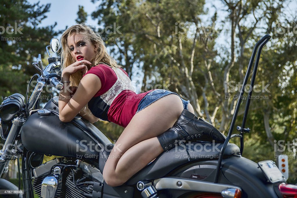 Sexy caucasian blond woman on motorcycle stock photo