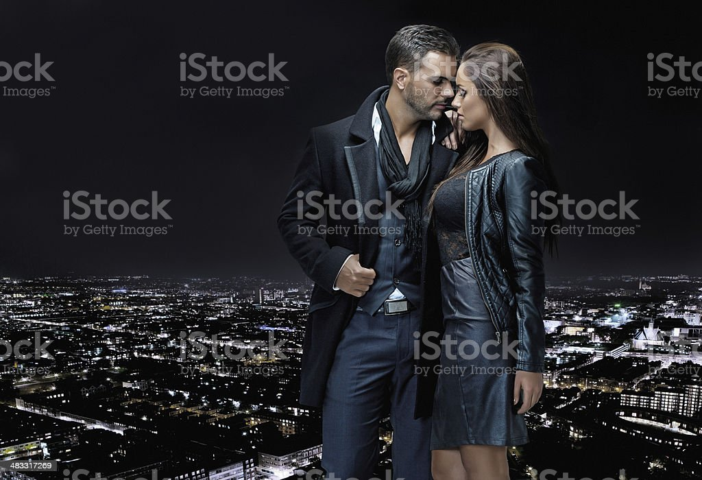 sexy couple posing on top of building in the night stock photo