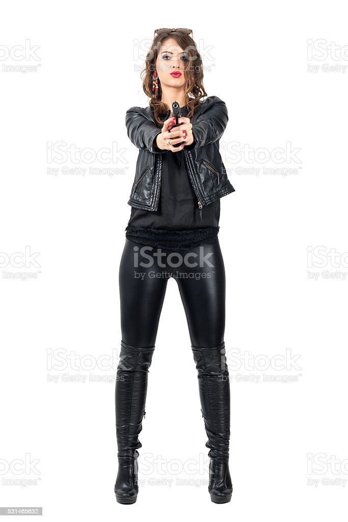 Sexy dangerous woman in leather boots pointing handgun at you stock photo