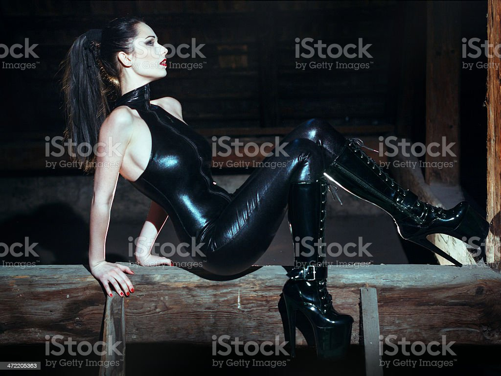 Sexy dominatrix at night posing on timber royalty-free stock photo