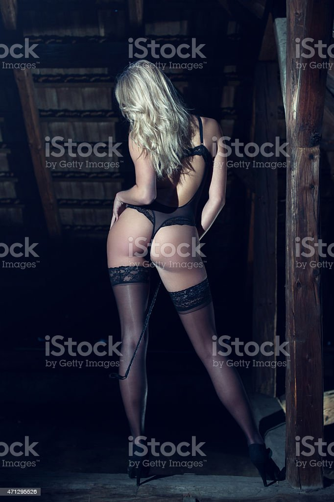 Sexy dominatrix with whip in barn stock photo