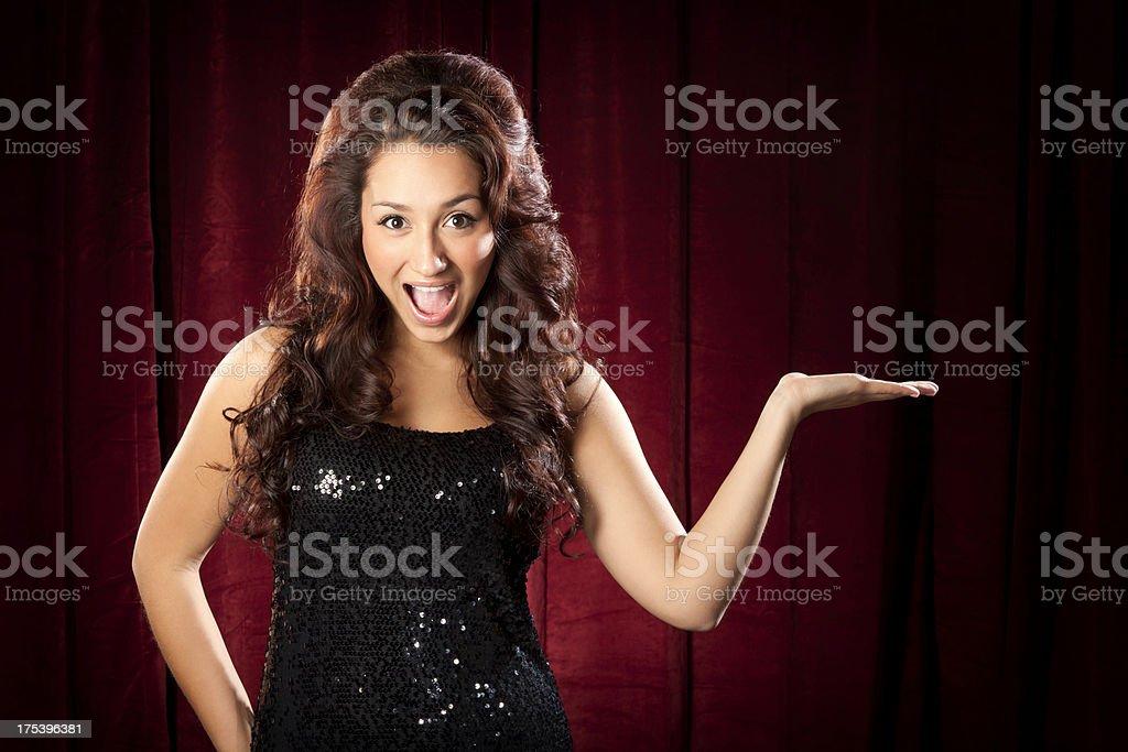 Sexy Enthusiastic Hispanic Woman Presenting on Stage stock photo