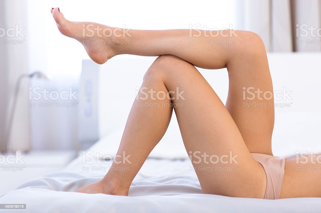 Sexy female legs on the bed stock photo