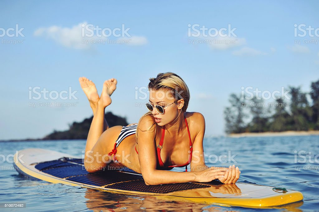 Sexy female model on surfboard in sea stock photo