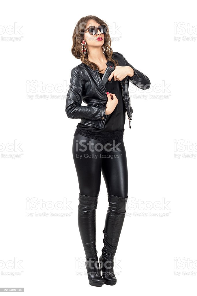 Sexy female spy wearing leather pulling handgun from her jacket. stock photo