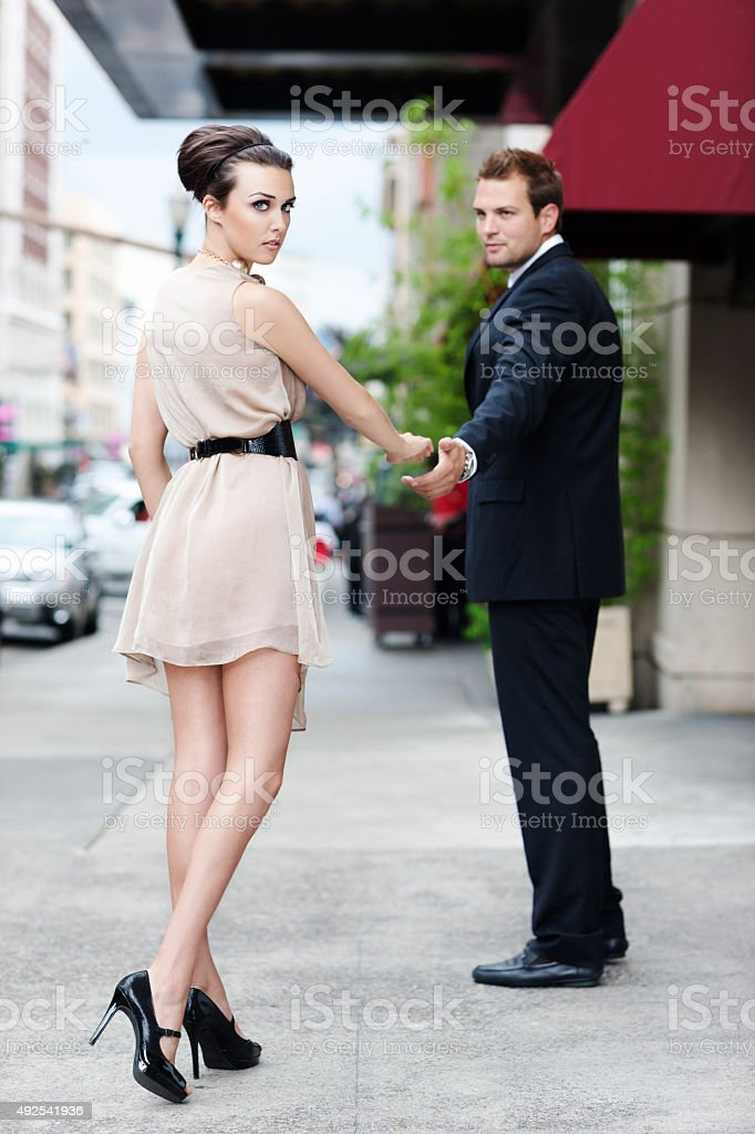 Sexy Girl in Dress with Long Legs Reaching for Boyfriend stock photo