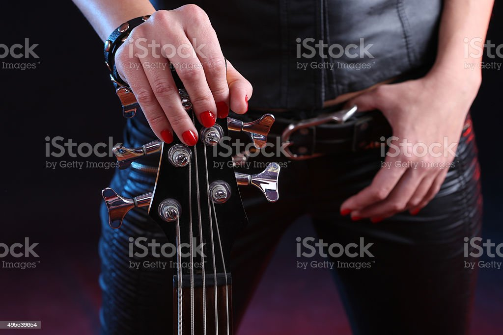 Sexy girl in leather clothes with bass guitar stock photo