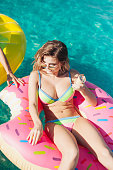 sexy girl in sunglasses eating ice cream in pool 20s.
