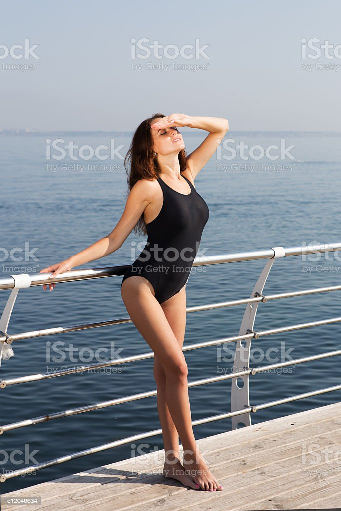 Sexy girl in swimsuit standing on the deck stock photo