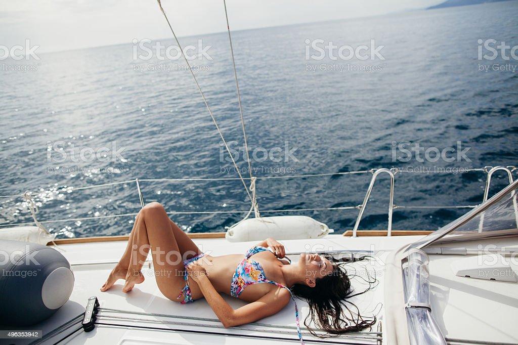 sexy girl in swimwear on yacht in tropics stock photo