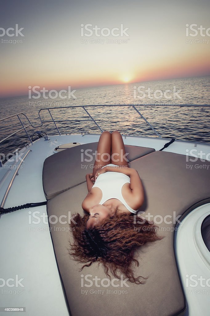 Sexy girl laying on yacht at dusk stock photo