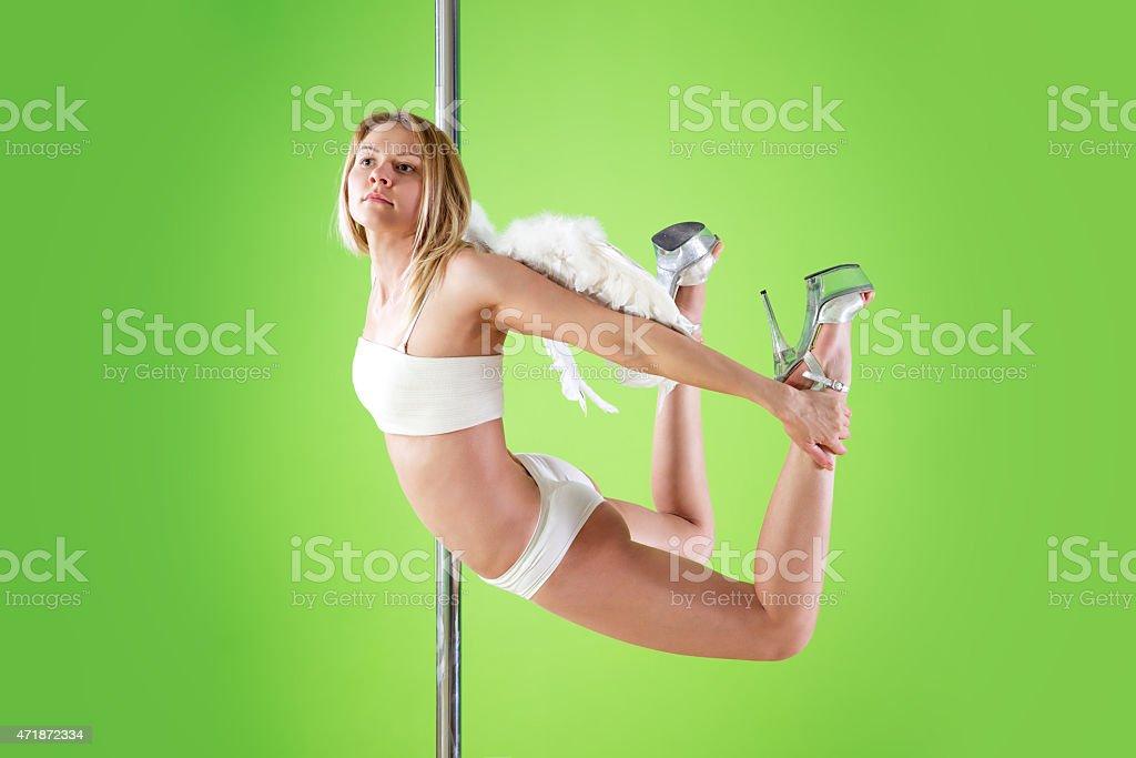 sexy girl makes  element yogini  at pole dance stock photo