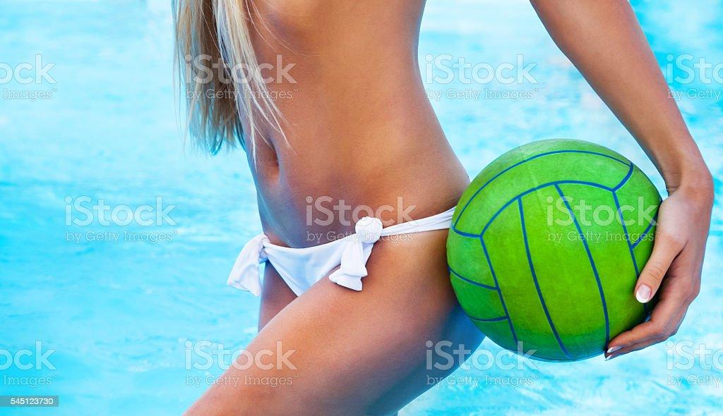 Sexy girl near the pool holding green ball stock photo