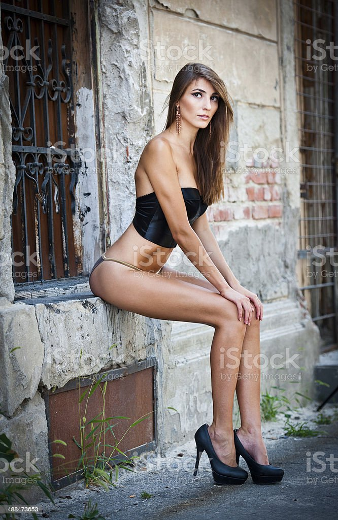 Sexy girl posing fashionable near red brick wall, urban shot stock photo