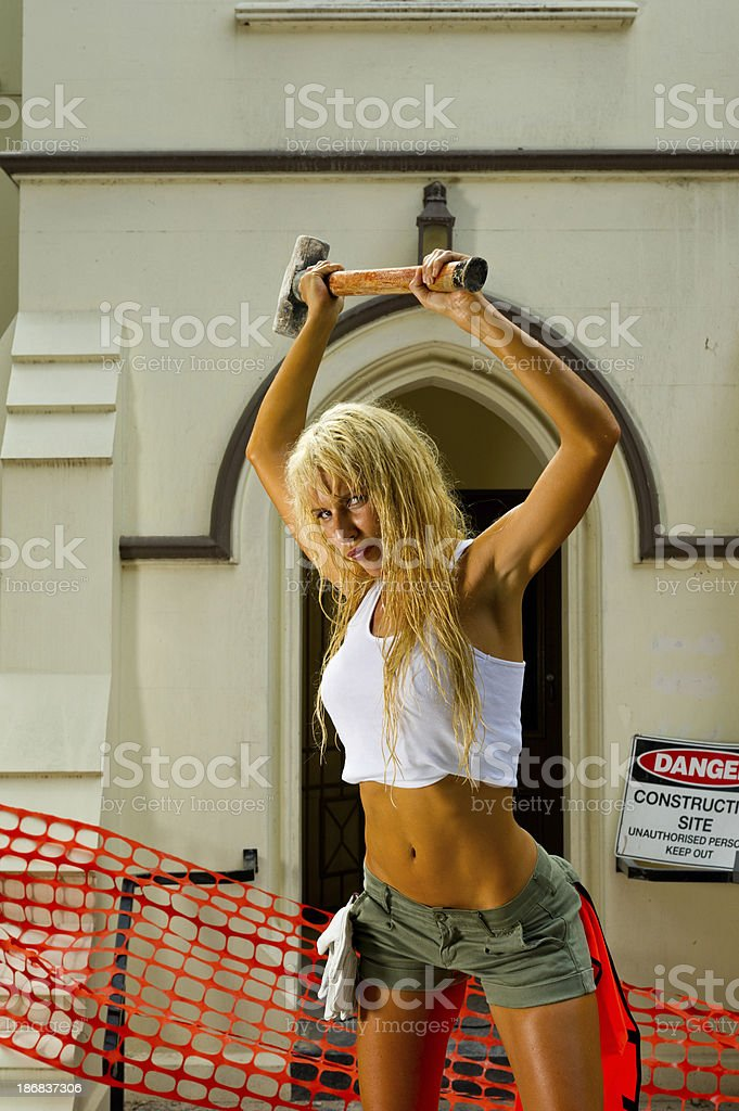 Sexy Girl swinging the sledgehammer on construcion site royalty-free stock photo
