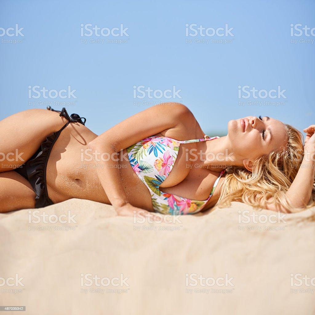 Sexy girl taking sunbath on the beach stock photo