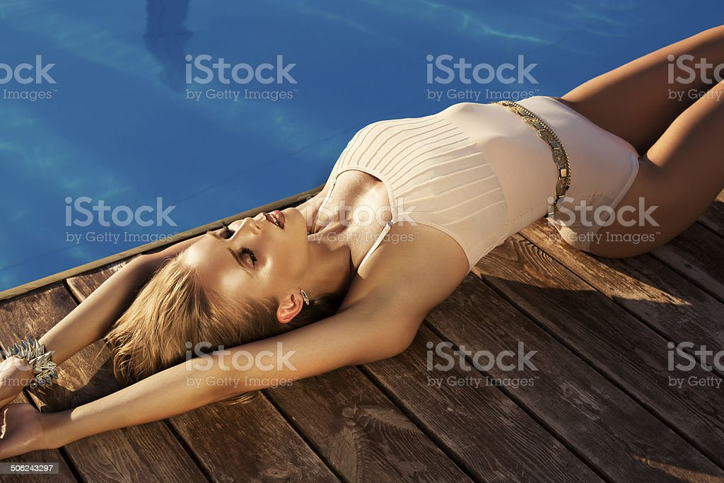 sexy girl with in swimsuite posing  beside a swimming pool stock photo