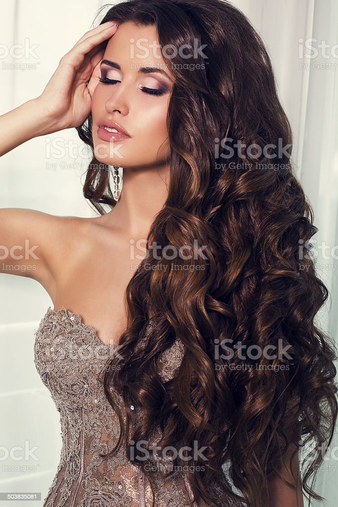 sexy girl with luxurious dark hair in elegant beige dress stock photo