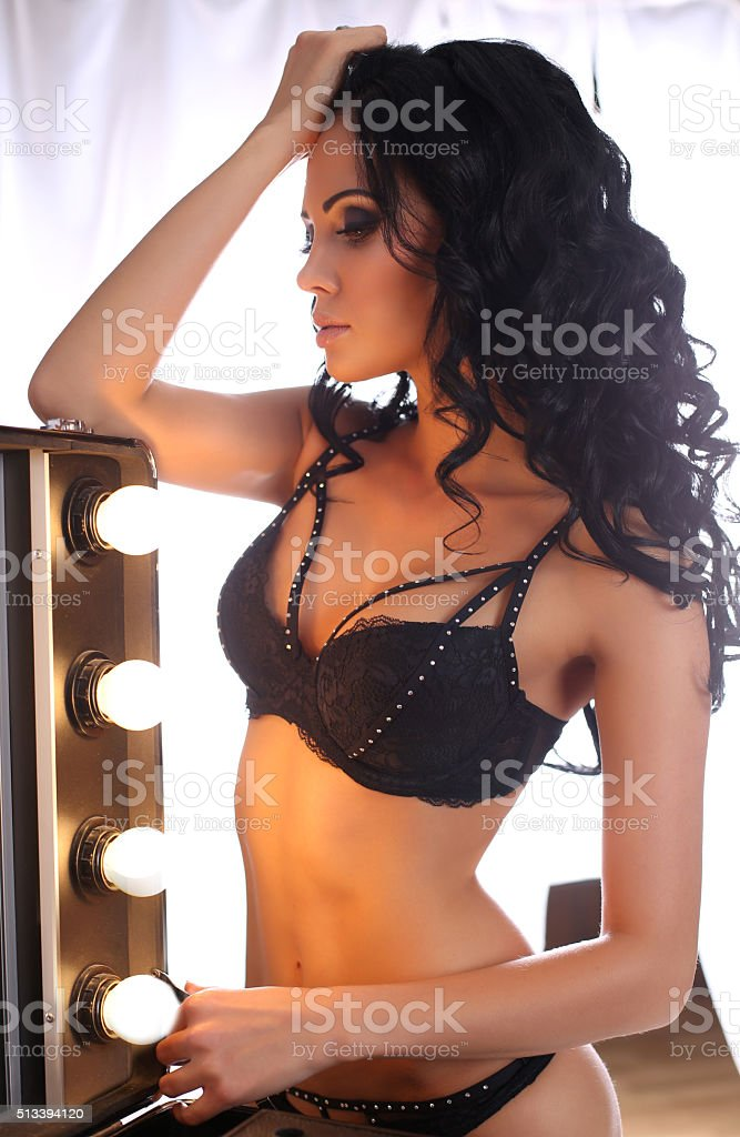 sexy glamour woman with dark hair wearing elegant black lingerie stock photo